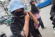 """Sept. 26, 2009 -- YALA, THAILAND: A Muslim woman puts on a motorcycle helmet after shopping in the market in Yala, Thailand. Thailand's three southern most provinces; Yala, Pattani and Narathiwat are often called """"restive"""" and a decades long Muslim insurgency has gained traction recently. Nearly 4,000 people have been killed since 2004. The three southern provinces are under emergency control and there are more than 60,000 Thai military, police and paramilitary militia forces trying to keep the peace battling insurgents who favor car bombs and assassination.  Photo by Jack Kurtz"""