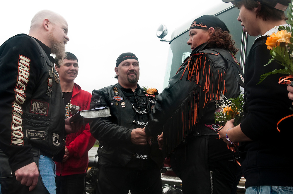 Matt Dixon | The Flint Journal..Pastor Brian McKay (left) of Victory Biker Church read vows to Pat and Kim Perge of Mt. Morris in the parking lot of the Perani Arena before riding in the 11th annual Bikin' for Burns fundraiser. The newlyweds and other bikers will ride 42 miles to Shriner's Circus Park in Vienna Township driving along Lapeer, Irish, Richfield, Genesee, Mt. Morris, Clio, Dodge, Jennings and Wilson Roads. The area event is sponsored by American Bikers Aiming Toward Education (ABATE) of Michigan Region 20 as they seek to promote motorcycle safety while raise funds for fire prevention. This year's recipients will be the Swartz Creek and Durand Fire Departments.