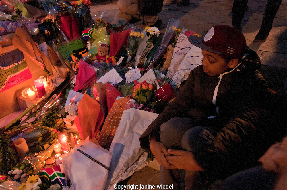 As a tribute to Nelson Mandela children and adults mourned his death and brought flowers & messages and lit candles beneath his statue in Parliament Square London