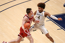 Feb 13, 2021; Morgantown, West Virginia, USA; Oklahoma Sooners guard Austin Reaves (12) drives against West Virginia Mountaineers guard Miles McBride (4) during the second half at WVU Coliseum. Mandatory Credit: Ben Queen-USA TODAY Sports