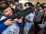 09 JANUARY 2016 - BANGKOK, THAILAND: A Thai boy plays with an Army IMI Tavor TAR-21 during Children's Day festivities at the Royal  Thai Army's Palace Guard, 2nd Division Cavalry Base in Bangkok. National Children's Day falls on the second Saturday of the year. Thai government agencies sponsor child friendly events and the military usually opens army bases to children, who come to play on tanks and artillery pieces.          PHOTO BY JACK KURTZ