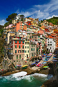 Riomaggiore is a village and comune in the province of La Spezia, situated in a small valley in the Liguria region of Italy. It is the first of the Cinque Terre one meets when travelling north from La Spezia.  The village, dating from the early thirteenth century, is known for its historic character and its wine, produced by the town's vineyards.  Riomaggiore is in the Riviera di Levante region and has shoreline on the Mediterranean's Gulf of Genoa, with a small beach and a wharf framed by tower houses. Riomaggiore's main street is Via Colombo, where numerous restaurants, bars and shops can be found.  The Via dell'Amore is a path connecting Riomaggiore to its frazione Manarola, also part of the Cinque Terre.<br /> Riomaggiore is the most southern village of the five Cinque Terre, all connected by trail. The water and mountainside have been declared national parks.