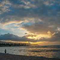 The sun sets over a beach walker on the northwest coast of Oahu, Hawaii.