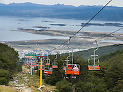 The ski lift above Ushuaia (in Tierra del Fuego province, in the southern Andes, Argentina, South America) gives views of the Beagle Channel, Ushuaia Airport, and Chile's Navarino Island. The foot of South America is known as Patagonia, a name derived from coastal giants, Patagão or Patagoni, who were reported by Magellan's 1520s voyage circumnavigating the world and were actually Tehuelche native people who averaged 25 cm (or 10 inches) taller than the Spaniards.