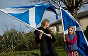 General election 2015. West Kilbride, Scotland. Eve of election calvacade around the town by the SNP (Scottish National Party). Two girls wave Saltaires ( Scottish flags).