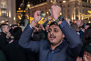 A Hindu man with small hand cymbals celebrates during a Hare Krishna street dance on New Years Eve at Piccadilly on the 31st December 2019 in London in the United Kingdom.