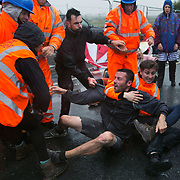 Day two of the Rolling Resistance, Preston New Road, Lancashire. Security violently try to prevent climate protectors to lock-on at the gates to Quadrilla drill site. One activists was restrained by the site manager using pressure points to the neck and throat and pinned to the ground by security staff on the road outside Quadrilla's property. Two activists managed to lock themselves down and block the gates.  A lock-on, where two or more lock themselves together inside a re-inforced tube is used as a peaceful non-violent way protesting. The New Preston Road Quadrilla site is almost ready to start drilling for shale gas after many delays caused by local objections. Lancashire County council voted against fracking but the conservative central government forced it through.