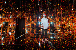 """© Licensed to London News Pictures. 17/05/2021. LONDON, UK. A Tate staff member views """"Infinity Mirrored Room – Filled with the Brilliance of Life"""", 2011, by Yayoi Kusama. Preview of Yayoi Kusama: Infinity Mirror Rooms on show at Tate Modern, in partnership with Bank of America with additional support from UNIQLO, from 18 May to 12 June 2022.  Photo credit: Stephen Chung/LNP"""