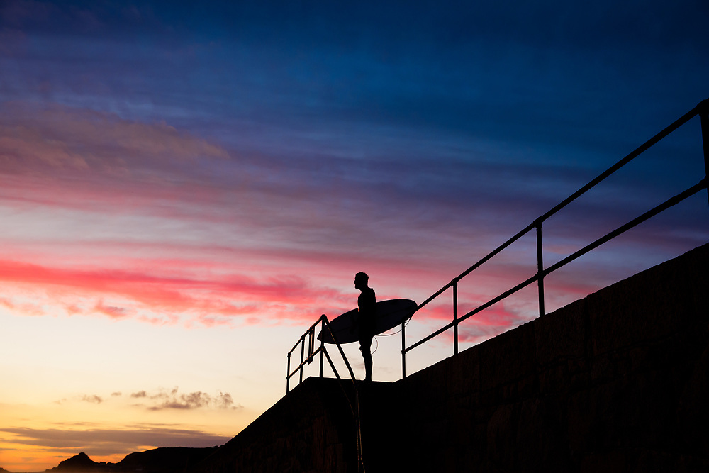 Surfer standing watching the waves under the red, pink sky of sunset at St Ouen's Bay, a popular beach with tourists in the Channel Islands