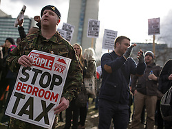 © Licensed to London News Pictures . 16/03/2013 . Manchester , UK . Former Gunner Cody Lachey (left, in fatigues) , who says he'll be made homeless by the new law . Protesters opposed to changes to housing benefit , known as the Bedroom Tax , hold an impromptu (unsanctioned) march through Manchester City Centre today (16th March) . The government plans to introduce changes to housing benefit from this April which will see some claimants receive a reduced amount if they have excess living space . Photo credit : Joel Goodman/LNP