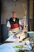 Portrait of a fish monger posing with the head of a swordfish at the Mercato del Capo, Palermo, Sicily.