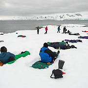 Tourists camp on the ice and snow at Hughes Bay on the Antarctic Peninsula.