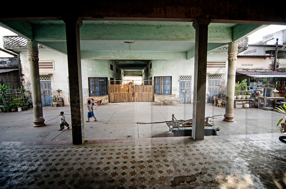 Abandoned Sengchaleun cinema, Savannakhet, Laos, Asia. Interiors are in complete decay and very messy. Kids walk through the yard