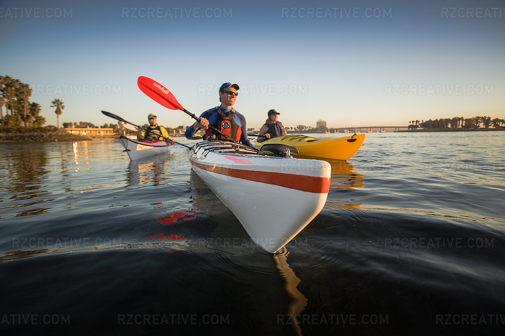 A group of sea kayakers paddling Mission Bay in San Diego in late afternoon light.