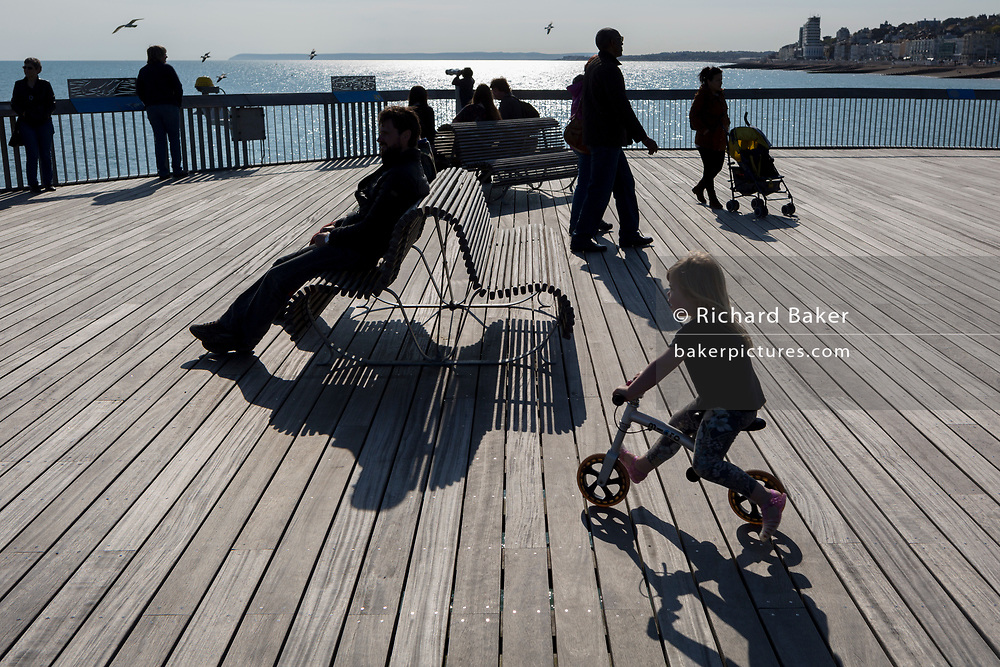 The figures of visitors including a biking girl with the shadows of a bench on Hastings Pier, on 29th April 2017, at Hastings, East Sussex, England.
