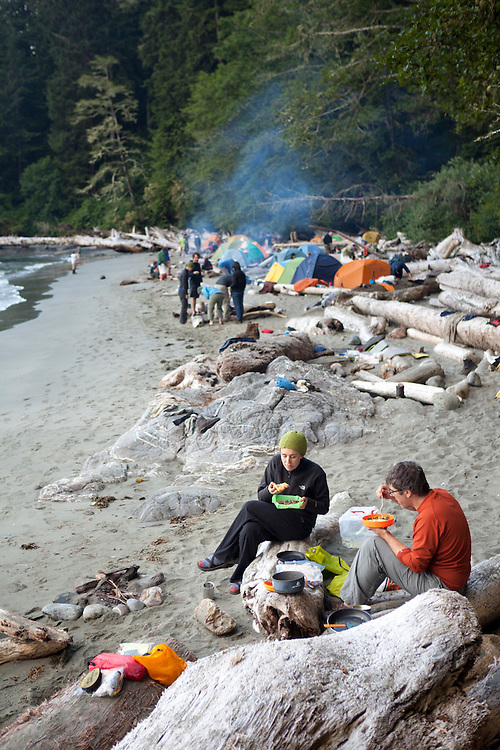 A couple eats dinner on the crowded beach campsite at Thrasher Cove, West Coast Trail, British Columbia, Canada.