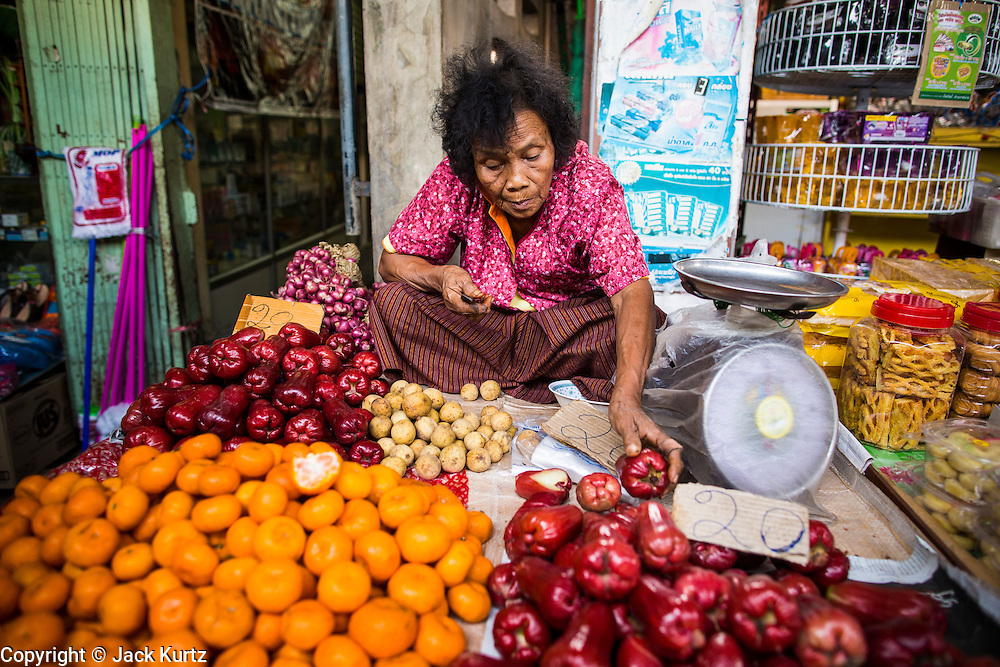 17 JANUARY 2013 - SAMUT SONGKHRAM, SAMUT SONGKHRAM, THAILAND: A fruit vendor in the Samut Songkhram market. Four trains each day make the round trip from Baan Laem, near Samut Sakhon, to Samut Songkhram, the train chugs through market eight times a day (coming and going). Each time market vendors pick up their merchandise and clear the track for the train, only to set up again when the train passes. The market on the train tracks has become a tourist attraction in this part of Thailand and many tourists stop to see the train on their way to or from the floating market in Damnoen Saduak.    PHOTO BY JACK KURTZ