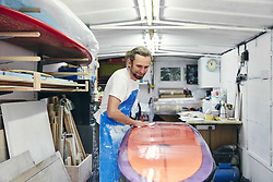March 24, 2018 - Man polishing and sanding a surfboard in a workshop (Credit Image: © Mint Images via ZUMA Wire)