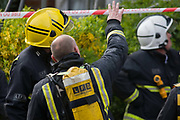 London Fire Brigade (LFB) firefighters attend a local minor roof fire in Herne Hill, south London. One fireman is wearing an oxygen tank on his back, equipped for BA (Breathing Apparatus) necessary to enter a burning building. The man discusses the incident with a senior officer whose raknk is denoted with 2 stripes on his helmet. They look upwards towards the roof deciding on the best and safest course of action.