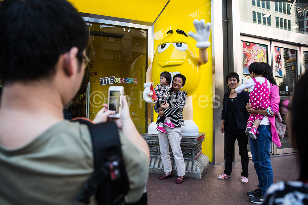 A woman holding a child poses for photographs in front of a statue of an M&Ms character in Shanghai, China, on Friday, Oct. 2, 2015.