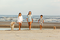 two sisters and their little brother walk on the beach with the family dogs