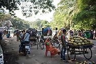 Dhaka, Bangladesh - November 1, 2017: A bustling street scene in Bangladesh's capital, Dhaka, with a motorbike, rickshaws, and a man selling green coconuts.
