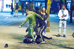 © Licensed to London News Pictures . 07/04/2017 . Manchester , UK . 8th in a sequence . Five youths on one as a fight breaks out in which a man's head is kicked and stamped upon , in Piccadilly Gardens . Greater Manchester Police have authorised dispersal powers and say they will ban people from the city centre for 48 hours , this evening (7th April 2017) , in order to tackle alcohol and spice abuse . Photo credit : Joel Goodman/LNP