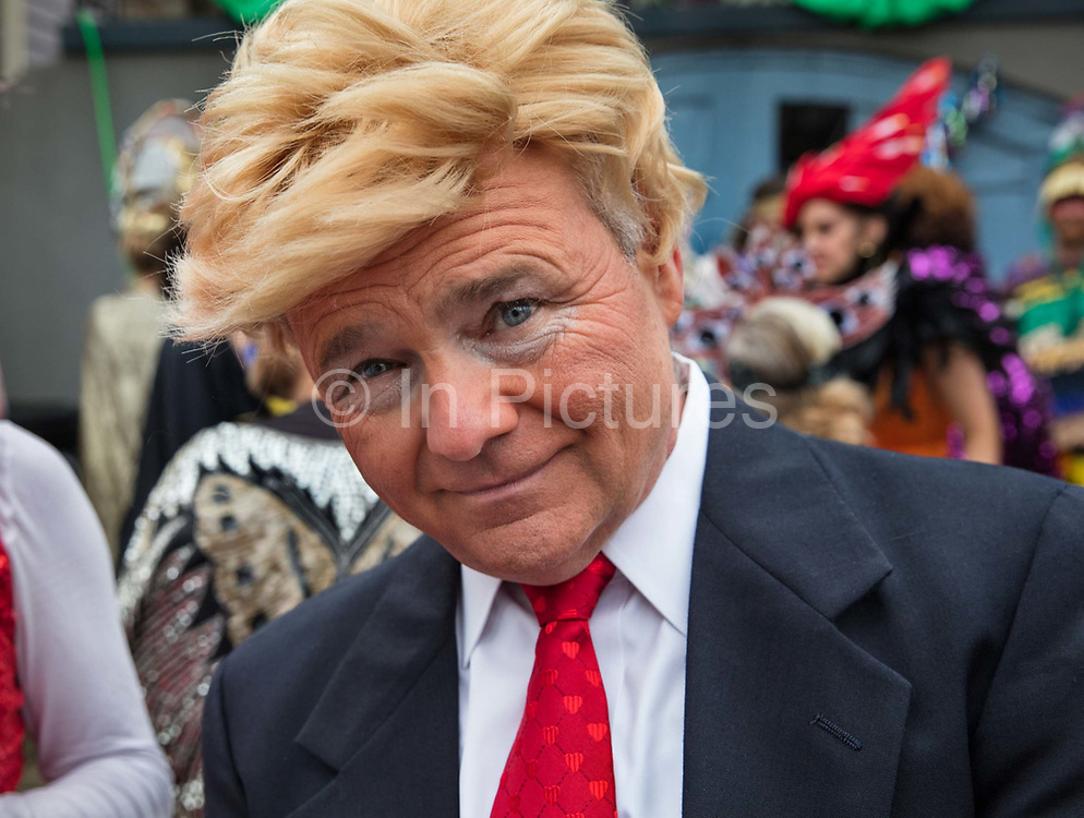 Trump impersonator with the Society of Saint Anne gathering to parade during Mardi Gras on 25th February 2020 in Bywater district of New Orleans, Louisiana, United States. Mardi Gras is the biggest celebration the city of New Orleans hosts every year. The magnificent, costumed, beaded and feathered party is laced with tradition and  having a good time. Celebrations are concentrated for about two weeks before and culminate on Fat Tuesday the day before Ash Wednesday and Lent.
