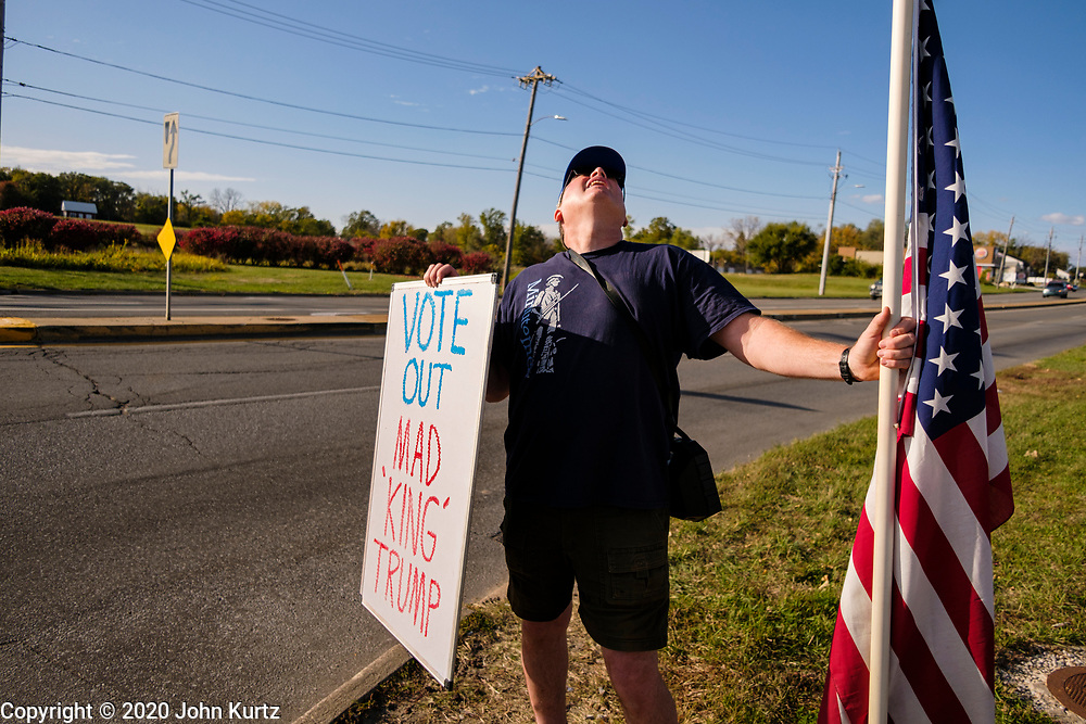 """14 OCTOBER 2020 - DES MOINES, IOWA: A man who identified himself as a """"Patriotic American"""" picketed the entrance of the Des Moines International Airport, where President Donald Trump spoke at a campaign rally. About 10,000 people were expected to attend the rally. Trump spoke at the rally, despite testing positive for COVID-19 less than three weeks ago. The rally did not meet the CDC guidelines for a safe gathering in the time of Coronavirus.        PHOTO BY JACK KURTZ"""