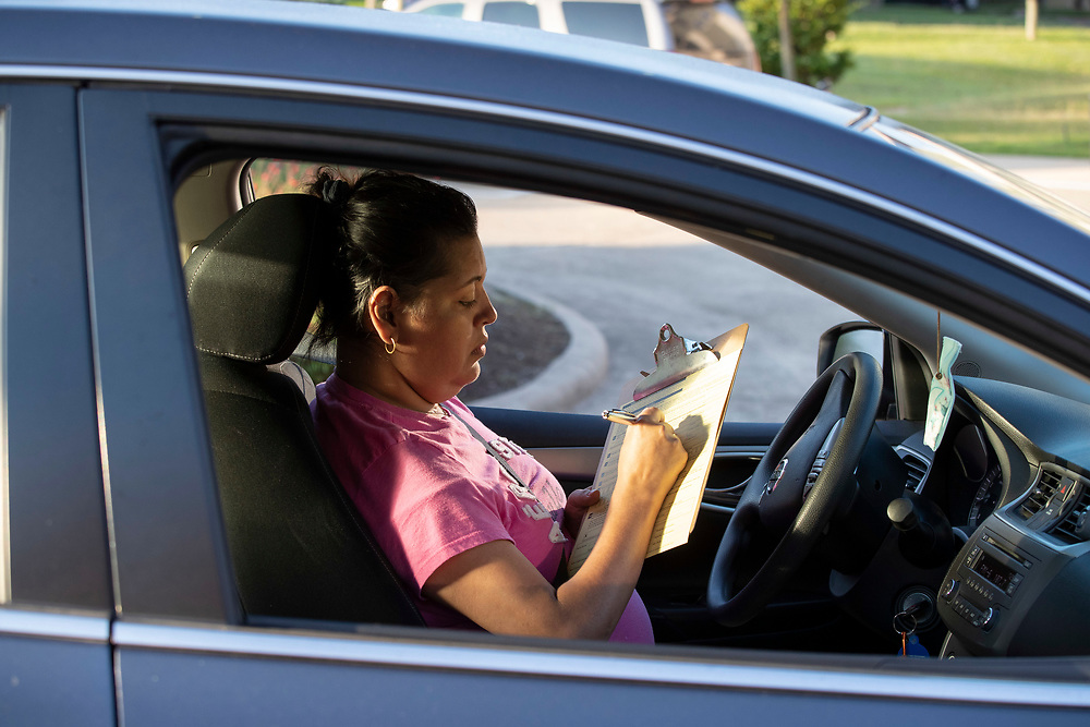 Austin resident Irma Flores fills out a voter registration application as Catholic Charities workers help Texas residents check voter registration status and help with voter applications during a four-hour drive October 1, 2020 in Austin.  Several dozen mostly Hispanic U.S. residents were signed up in the non-partisan effort.
