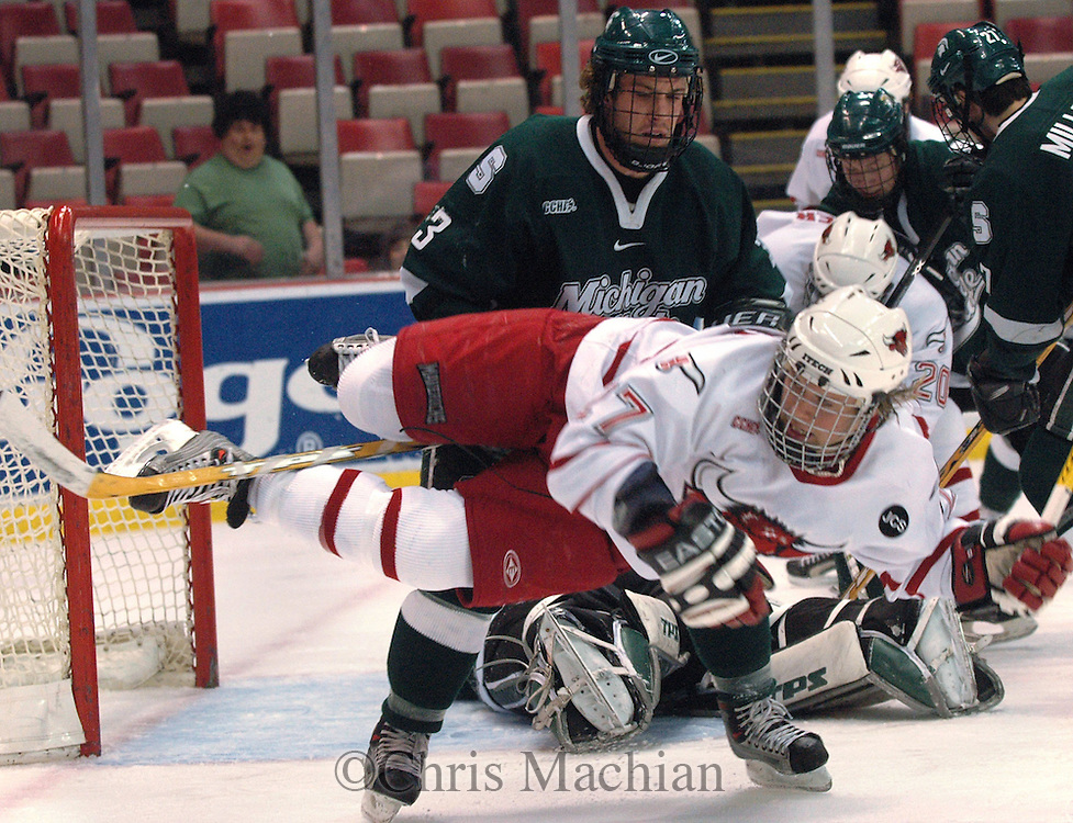 03/17/05 Detroit Michigan.  Univ of Nebr at Omaha's Lawrence  gets tripped up by Michigan State's Chris Snavely during the first period Thursday night during the first game of the CCHA Super Six at Joe Louis Arena.