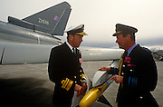 A Royal Navy Admiral and an RAF Air Chief Marshal inspect a missile of a Eurofighter (now called Typhoon) fighter jet. The Eurofighter Typhoon is a twin-engine, canard-delta wing, multirole combat aircraft, designed and built by a consortium of three companies. Its maiden flight took place on 27 March 1994 watched by VIPS from UK industry and military.