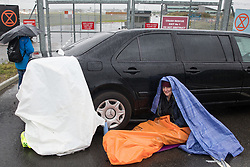 An Extinction Rebellion climate activist sits locked to a stretch limousine blocking an entrance to Farnborough Airport on 2nd October 2021 in Farnborough, United Kingdom. Activists blocked three entrances to the private airport to highlight elevated carbon dioxide levels produced by super-rich passengers using private jets and 'greenwashing' by the airport in announcing a switch to sustainable aviation fuel (SAF).