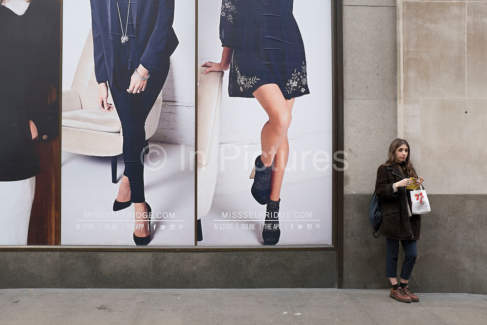 Girl rolling and smoking a cigarette while standing beside some large scale advertising pictures outside a fashion store. London, UK.