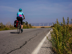 Rear view of woman mountain biker riding on road