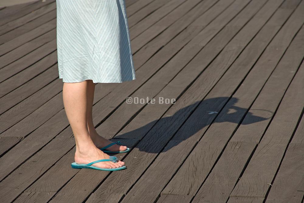 woman standing on a wooden boardwalk