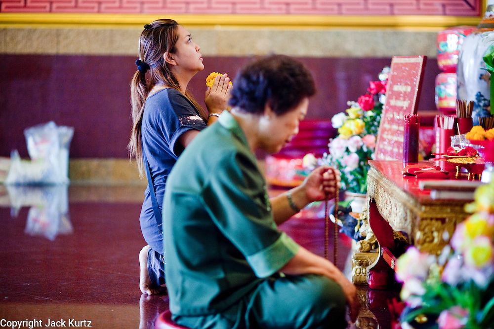07 OCTOBER 2009 -- BANGKOK, THAILAND: People praying at the Kuan Yim Shrine in Chinatown, Bangkok, Thailand. The shrine was founded by and is maintained by the Thian Fa Foundation, one of the first charitable foundations in Bangkok to provide medical care for the poor. Chinatown is the old commercial heart of Bangkok with thousands of small shops selling everything from clothes to dried fish to case lots of shoes and gem stones.   Photo By Jack Kurtz