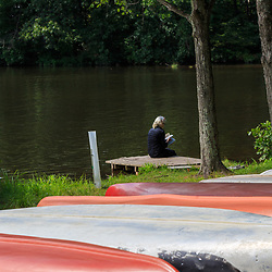 Mt. Gretna, PA, USA - August 23, 2015: A woman reads a book on the dock at the lake.