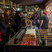 BUDAPEST, HUNGARY - DECEMBER 07:  Customers buy the traditional Hungarian Chimney Cake (Kurtoskalacs) at Vorosmarty Square Christmas market on December 7, 2017 in Budapest, Hungary. The traditional Christmas market and lights will stay until 31st December 2017.
