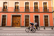 Cyclists ride down a street in the historic district of Mexico City, Mexico.