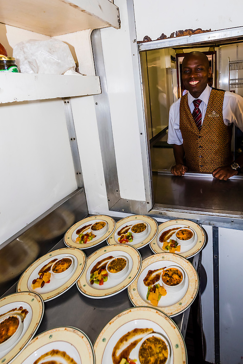 Waiters preparing to serve the first course (Bobotie, a spiced beef mince dish) of lunch aboard the luxury Rovos Rail train between Pretoria and Cape Town, South Africa.