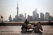 With the skyscrapers of Pudong's Lujiazui Financial District across the Huangpu River, a worker drives a tractor through a construction site, a part of the historical riverside Bund renovation project underway for the upcoming World Expo in Shanghai, China on 27 May 2009.  60 years ago today residents of Shanghai woke up to find communist soldiers sleeping on the streets as the People's Liberation Army drove away the defending Nationalists after 15 days of intense fighting using only light weaponry to minimize collateral damage.