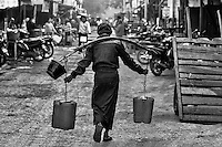 The Burden of Reality (B&W): A man continues his solitary, life-long and unchallenged station in life; with the unrelenting burden of fate, he finds himself wearing a wooden yoke hauling two pails of water down a nearly deserted market street, Nyaung U Myanmar.