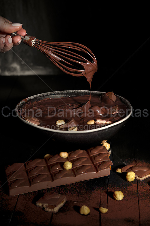 Woman hand with whisk mixing melted chocolate with peanuts in a bowl<br />  <br /> This file is only available at Stockfood.com see the Licensor link below
