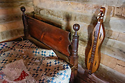 A dulcimer hangs by a quilted bed in the cabin interior at Humpback Rocks Mountain Farm, a restored 1890s farmstead open to the public at Milepost 5.8 on the Blue Ridge Parkway, in Virginia, in the Blue Ridge Mountains (a subset of the Appalachian Mountains), USA. In summer, costumed interpreters demonstrate 1890s southern Appalachian mountain life. European settlers of the Appalachian Mountains forged a living from abundant native materials: hickory, chestnut, and oak trees provided nuts for food, logs for building, and tannin for curing hides; and the rocks were used as foundations, chimneys and stone fences. This farm was originally a Land Grant tract dispensed by the Commonwealth of Virginia to induce pioneers to settle; and later it became known as the William J. Carter Farm. The scenic 469-mile Blue Ridge Parkway was built 1935-1987 to aesthetically connect Shenandoah National Park (in Virginia) with Great Smoky Mountains National Park in North Carolina, following crestlines and the Appalachian Trail.