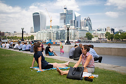 © Licensed to London News Pictures. 26/07/2018. London, UK. Office workers in London Bridge relax outside during hot weather. Today is predicted to be the hottest day of the year, with temperatures in the capital set to rise up to 35 degrees, as the UK experiences a prolonged heatwave. Photo credit : Tom Nicholson/LNP