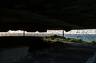 """View at sunset from inside a German coastal bunker, part of the """"Atlantic Wall"""", at Pointe du Hoc, Normandy, France. On D-Day (6 June 1944) the United States Army Ranger Assault Group successfully assaulted Point du Hoc after scaling the cliffs."""