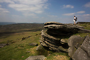 A lone female walker rests on top of Stanage Edge gritstone cliffs. From the summit of this escarpment, we see a wide landscape of Gritstone geology on Long Causeway cliffs, Derbyshire. This is the top of Stanage Edge gritstone cliffs. Beyond is a beautiful panorama of the Peak District National Park in England. Stanage Edge is the largest of the gritstone edges that overlook Hathersage in Derbyshire. Stanage Edge at approximately 4 miles in length and 458m at its highest point is the largest of the gritstone cliffs that overlook Hathersage, Derbyshire. The area is one of the most popular locations in the Peak District National Park for climbing and walking with hundreds of rock climbing routes to challenge all ranges of ability. Walkers are drawn to the area to enjoy the varied moorland scenery with stunning views across the surrounding countryside.
