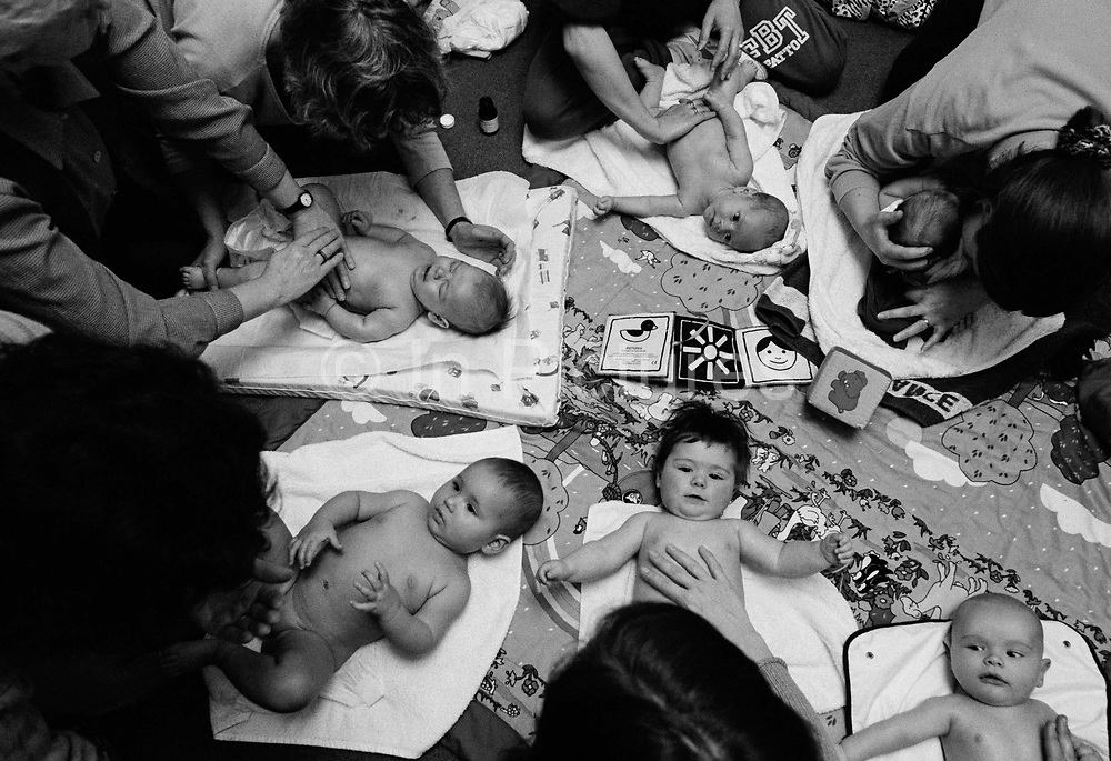 """""""The week of Dunblane.""""  Mindful of the Dunblane massacre that week, a baby massage class takes place at a health clinic in south London. Spread across a matt are six babies of varying ages and sizes whose mums are tenderly stroking their infants' bodies and senses with soft, gentle touches over the head, face, shoulders, arms, chest, stomach and legs which is a recommended way of tactile communication between mother and child. Some children are looking up into their mothers' faces, others are looking elsewhere and one is upset but comforted. This is from a documentary series of pictures about the first year of the photographer's first child Ella. Accompanied by personal reflections and references from various nursery rhymes, this work describes his wife Lynda's journey from expectant to actual motherhood and for Ella - from new-born to one year-old."""