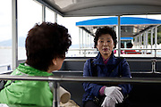 "Two women waiting for transport to Odongdo island in Yeosu which is connected to the shore by a 768-meter-long breakwater. Yeosu will host the Expo 2012 exhibition  under the theme ""The Living Ocean and Coast"". Yeosu (Yeosu-si) is a city in South Jeolla Province. Old Yeosu City, which was founded in 1949, Yeocheon City, founded in 1986, and Yeocheon County were merged into a new city in 1998."